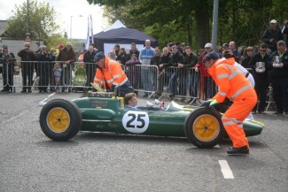 Allan McNish in John Bowers' Lotus 25 being turned round before taking a second run up the street