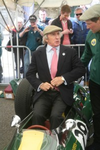 Jackie Stewart takes off his blazer before getting into the ex-Jim Clark Lotus 25 now owned by Nick Fennell, right