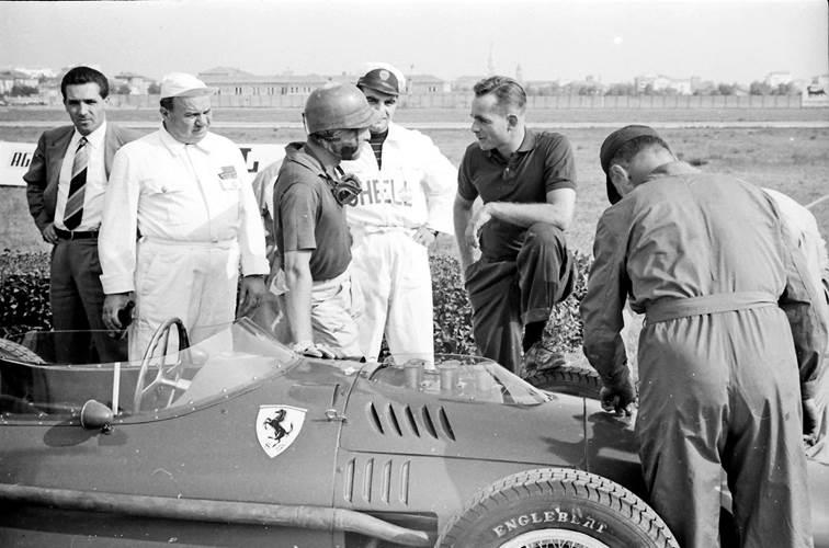 Phil Hill in sports shirt talks to Peter Collins on the grid at the 1957 Modena Grand Prix whilst portly mechanic Parenti looks on.