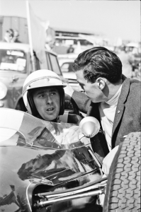 Jackie sitting in a Formula 1 car for the first time. Jim Clark gives him some advice before an impromptu run after practice during the British Grand Prix meeting 1964