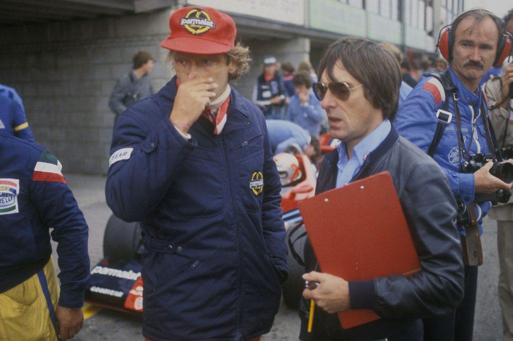 Niki Lauda and Brabham-Alfa Romeo team principal Bernie Ecclestone in the pits during practice for the 1978 Dutch Grand Prix in Zandvoort. Behind them are John Watson (in car) and photographer Nigel Snowdon. Photo: Grand Prix Photo