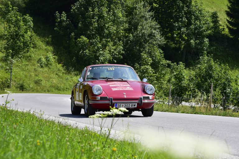 Racing driver Jo Ramirez driving a red Porsche 912 in green forest, our highest placed member