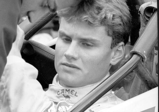 Black and white photo of a young David Coulthard sitting in the Formula Vauxhall Lotus car of Paul Stewart Racing