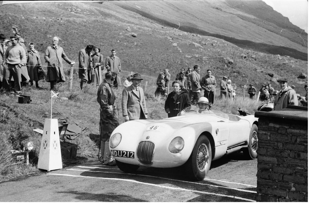 When Michael Head sold his C type Jaguar it was bought by Rosemary Vickers, seen here in duffel coat at Rest and Be Thankful hill climb in 1955 when she loaned it to Ecurie Ecosse driver Ninian Sanderson to run. (Graham Gauld)