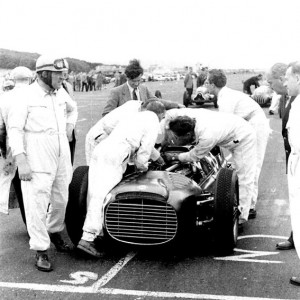 Reg Parnell, left, waits on the grid at Turnberry Circuit in 1952 whilst the BRM Mechanics work on the complex CRM V16 grand prix car.