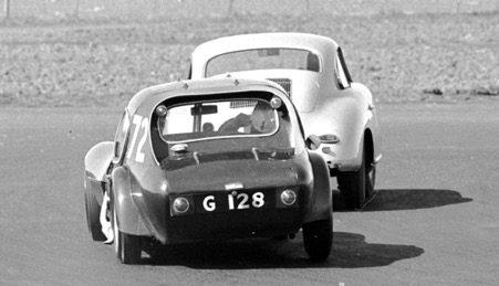 Jackie Stewart in action with the Marcos chasing Gordon Durham's Porsche Carrera in 1961. The Marcos is now owned by Matteo Panini