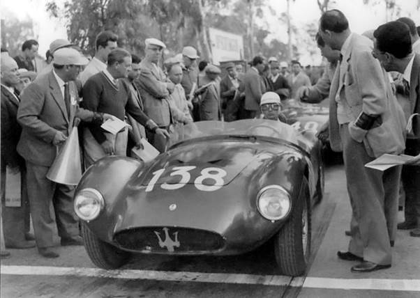 black and white photo of A group of people standing around a 1959 Maserati 6GCS Racing car