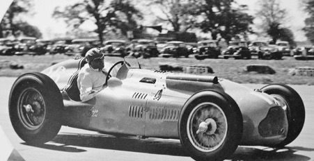 A vintage photo of a person driving a car  Description automatically generated